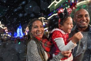 Mom, dad, and daughter enjoying snowfall at Mickey's Very Merry Christmas Party