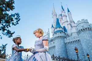 Young girl in Cinderella dress meets Cinderella in front of her castle at Magic Kingdom Walt Disney World