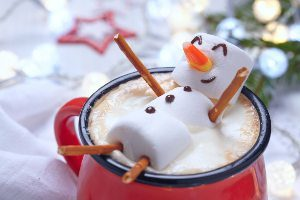 Marshmallow snowman floating in a mug of hot chocolate