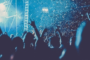 Crowd in blue light at concert waving their arms in the air as confetti falls